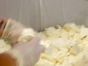 Breaking the curd by hand in the draining table.